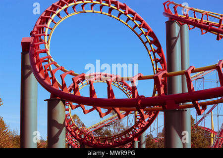 A looping, twisting, red steel rollercoaster thrills passengers with speed and turns. - Stock Photo