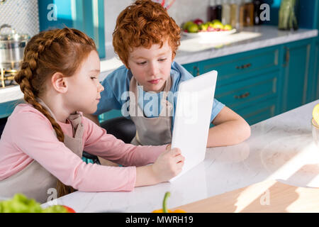 adorable children in aprons using digital tablet while cooking together in kitchen - Stock Photo