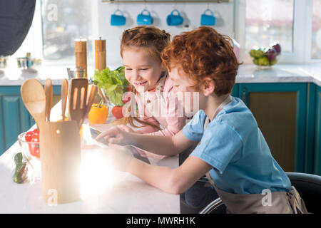 happy children using digital tablet while cooking together in kitchen - Stock Photo