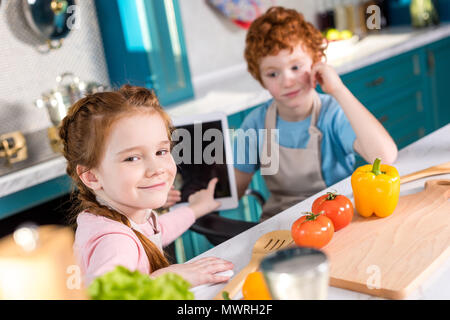 children using digital tablet while cooking together in kitchen - Stock Photo