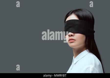 young woman wearing black blindfold isolated on grey - Stock Photo