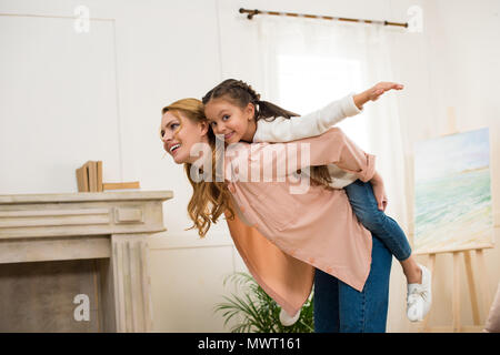 happy mother piggybacking adorable little daughter at home - Stock Photo