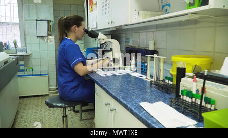 Woman lab assistant working with a microscope in Laboratory. Female scientist looking through a microscope in lab. Scientist using a microscope in a laboratory. - Stock Photo