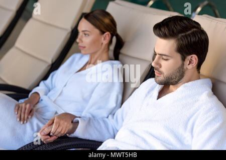 young couple in bathrobes holding hands while resting together in spa center - Stock Photo