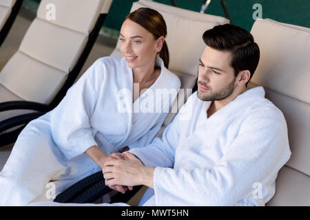 happy young couple in bathrobes holding hands and looking away in spa center - Stock Photo