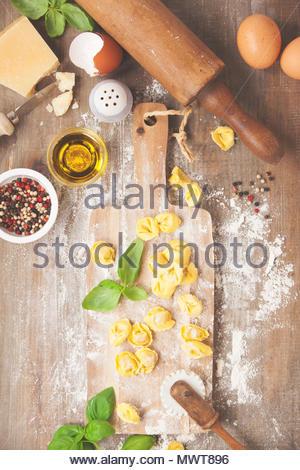 raw italian pasta tortellini on wooden board - Stock Photo