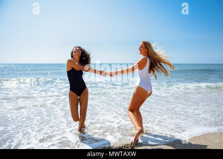 a12acbcf97914 Two young women with beautiful bodies in swimwear having fun with their  hands caught on the