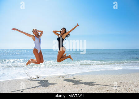 Two funny girls with beautiful bodies in swimwear jumping on a tropical beach. Funny caucasian and arabic females wearing black and white swimsuits. - Stock Photo