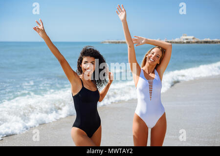 Two young women with beautiful bodies in swimwear on a tropical beach. Funny caucasian and arabic females wearing black and white swimsuits waving wit - Stock Photo
