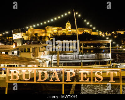 Budapest on the River Danube at night, with Buda Royal Palace aka Buda Castle in the background, Hungary. - Stock Photo