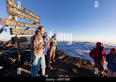 Climbers at summit sign and views on Mount Kilimanjaro, Kilimanjaro National Park, UNESCO World Heritage Site, Tanzania, East Africa, Africa - Stock Photo