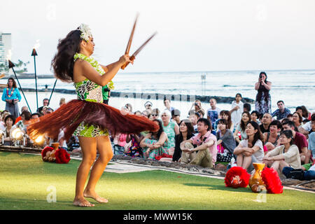 Hawaii Hawaiian Honolulu Waikiki Beach Kuhio Beach Park Hyatt Regency Hula woman dancing dancer dance audience watching Pacific Ocean Waikiki Bay - Stock Photo