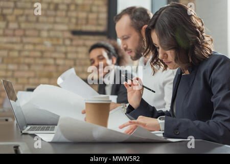 team of architects working on building plans at modern office - Stock Photo