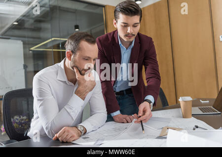 thoughtful architects brainstorming over building plans at office