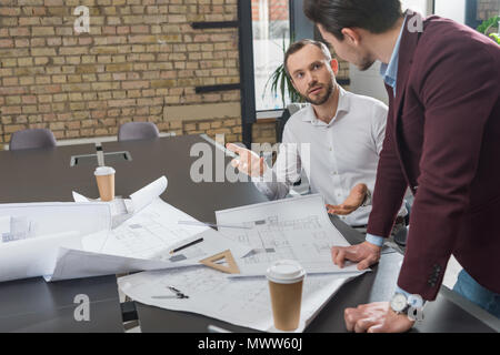 successful architects brainstorming over building plans at office