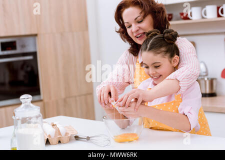grandmother with little granddaughter preparing dough for cooking at kitchen - Stock Photo