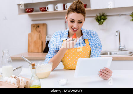 attractive young woman eating strawberry and using tablet at kitchen while cooking - Stock Photo