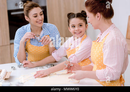 three generations of beautiful women cooking together at kitchen - Stock Photo