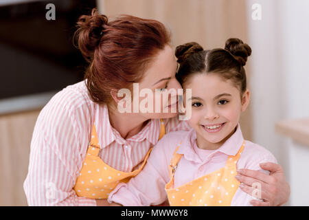 grandmother embracing little granddaughter while cooking in aprons - Stock Photo
