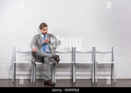 caucasian businessman checking time while waiting for job interview - Stock Photo