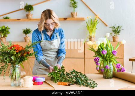beautiful young florist in eyeglasses arranging flowers at workplace - Stock Photo