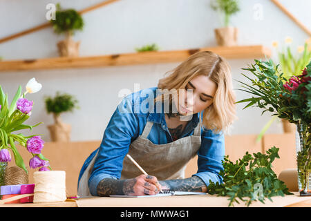 beautiful young female florist taking notes at workplace - Stock Photo