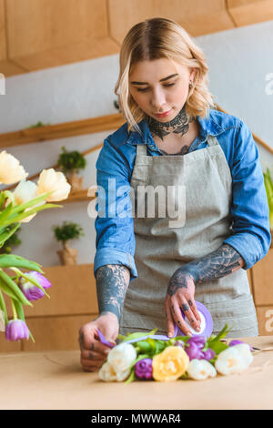 beautiful young florist arranging tulip flowers at workplace - Stock Photo