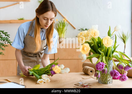 young florist in apron arranging beautiful tulip flowers at workplace - Stock Photo