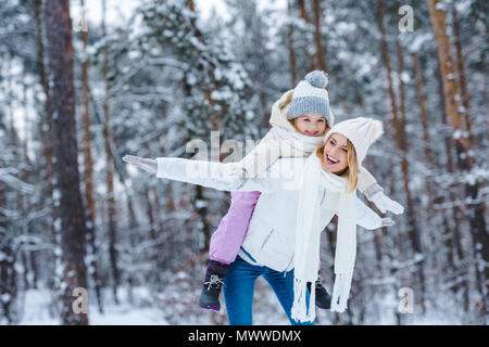 cheerful mother and little kid piggybacking together in winter park - Stock Photo