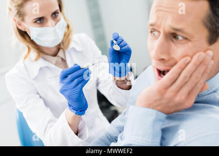 Male patient is afraid of dentist in modern dental clinic - Stock Photo
