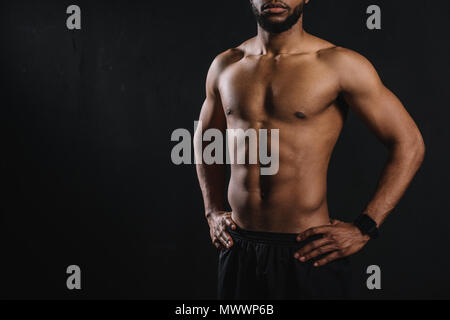 cropped shot of muscular shirtless man standing with hands on waist ...