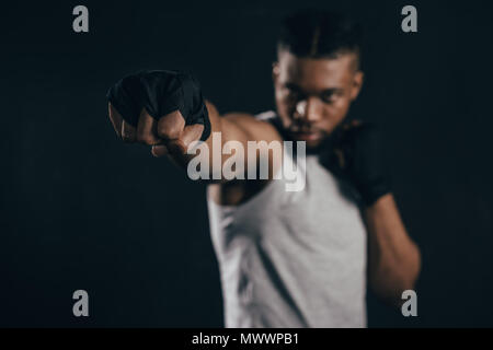 close-up view of young african american kickboxer training on black - Stock Photo