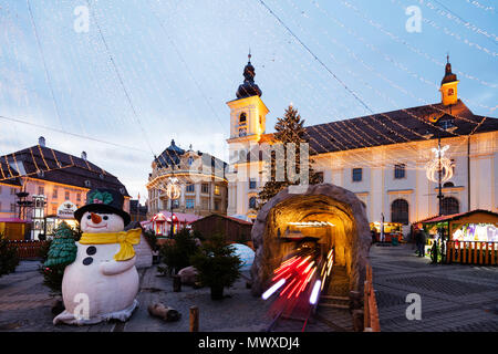 Christmas market in Plaza Piata Mare, City Hall and Baroque Jesuit Church, Sibiu, Romania, Europe - Stock Photo