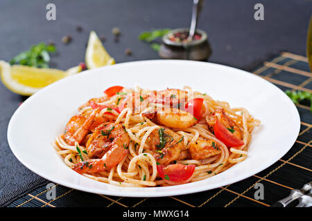 Pasta spaghetti with shrimps, tomato and parsley. Healthy meal. Italian food. - Stock Photo