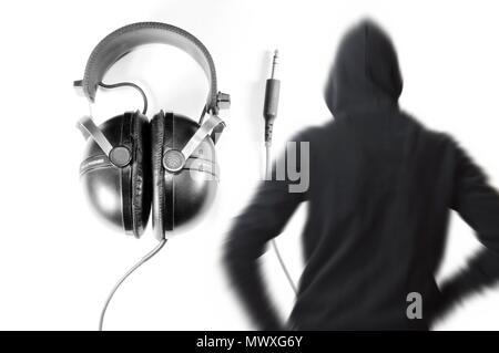 Headphone in background and black and white blurred vintage silhouette of young man with hooded sweatshirt. Dj concept. - Stock Photo