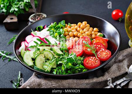 Salad of chickpeas, tomatoes, cucumbers, radish and greens. Dietary food. Vegan salad. - Stock Photo