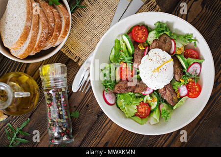 Warm salad from chicken liver, radish, cucumber, tomato and egg poached. Healthy food. Dietary menu. Top view. Flat lay. - Stock Photo