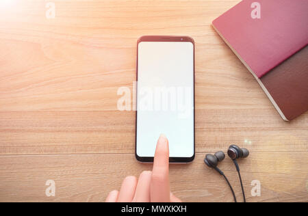 Technology concept, Woman hand holding smartphone on wood table with black headphone cable background,top view. - Stock Photo