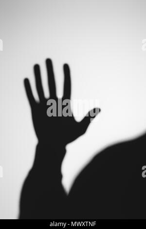 strange blurry shadow of human hand on grey - Stock Photo