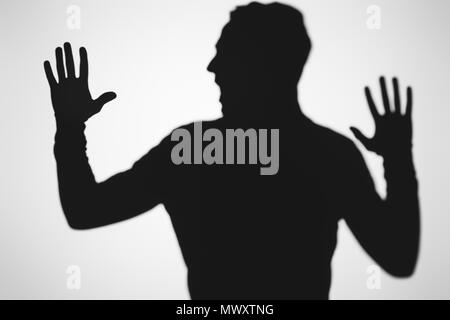 scary blurry shadow of person screaming on grey - Stock Photo