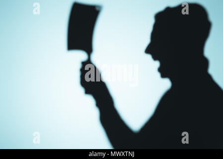scary shadow of screaming person holding meat knife on blue - Stock Photo