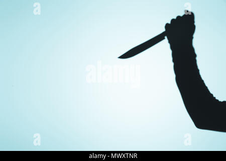 spooky shadow of person holding knife in hand on blue - Stock Photo