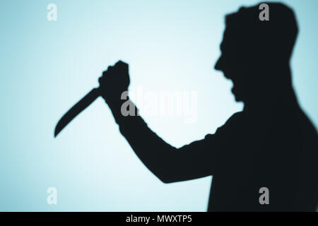 shadow of person screaming and holding knife on blue - Stock Photo