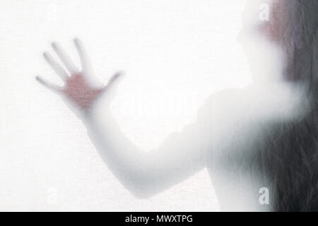blurry silhouette of screaming person touching frosted glass - Stock Photo