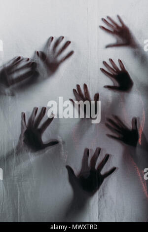 blurry scary silhouettes of human hands touching frosted glass - Stock Photo