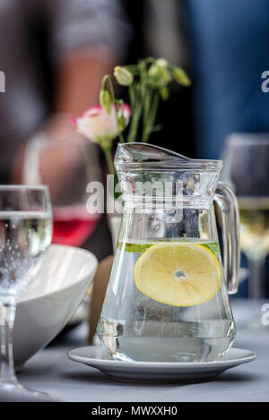 Table laying concept. On the table stands a jug with water and lemon. Glasses in the background. - Stock Photo
