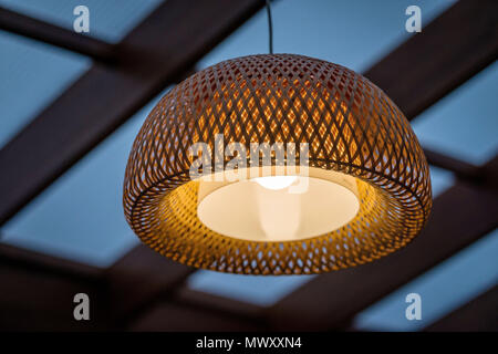 Interior of the outdoor terrace with a wicker wood ceiling lamp. - Stock Photo