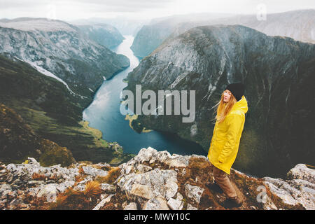 Woman traveler on mountain cliff standing alone traveling in Norway Lifestyle adventure vacations aerial fjord view girl wearing yellow raincoat walki - Stock Photo
