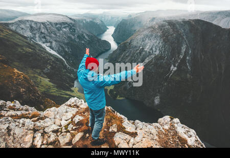 Brave traveler man raised hands traveling in Norway standing on cliff mountain active lifestyle weekend getaway adventure vacations success concept ae - Stock Photo