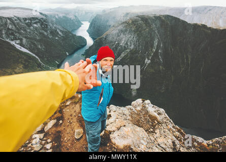 Couple adventurers in mountains follow helping hand traveling together lifestyle concept extreme vacations adventure weekend getaway in Norway - Stock Photo